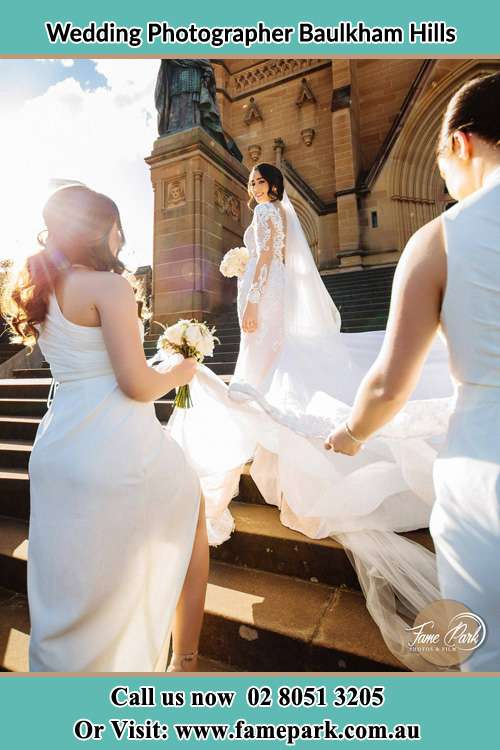Photo of the Bride smiling at her bridesmaid holding the tail of her gown at the front of the church Baulkham Hills NSW 2153