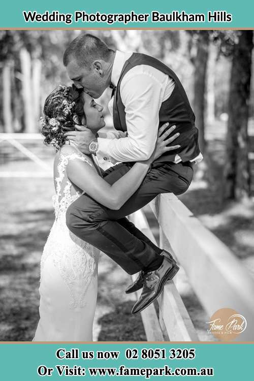 Photo of the Groom sitting on the fence kissing the bride at the forehead Baulkham Hills NSW 2153
