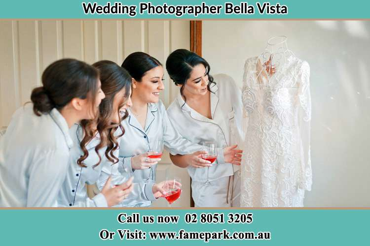 Photo of the Bride and the bridesmaids checking the wedding gown Bella Vista NSW 2153