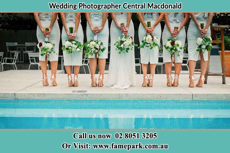Behind photo of the Bride and the bridesmaid holding flower near the pool Central Macdonald NSW 2775