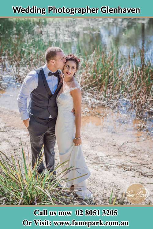 Photo of the Groom kiss the Bride near the lake Glenhaven NSW 2156
