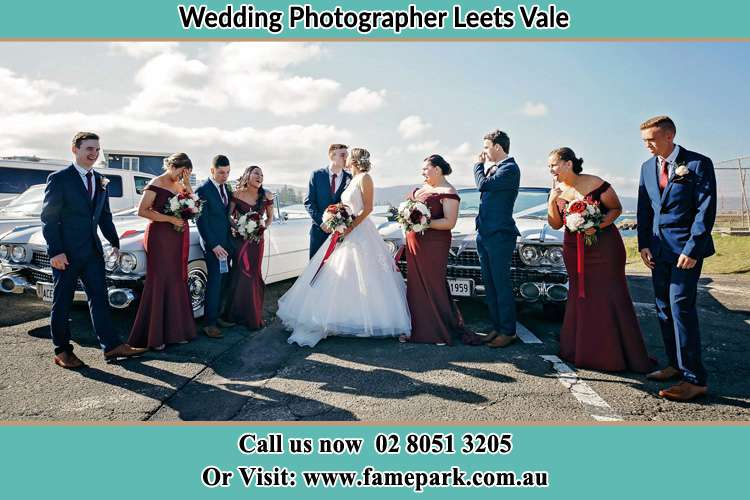 Photo of the Groom and the Bride kissing with the secondary sponsors at the parking lot Leets Vale NSW 2775