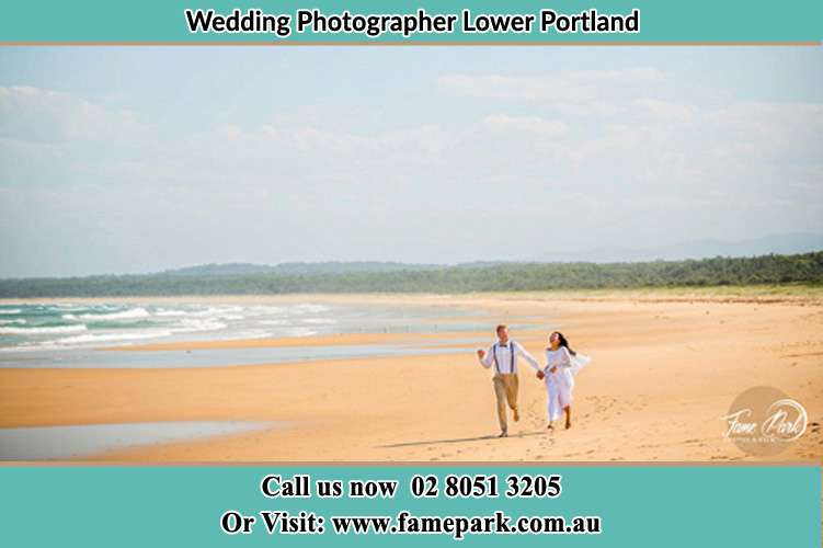 Photo of the Groom and the Bride walking down the sea shore Lower Portland NSW 2756