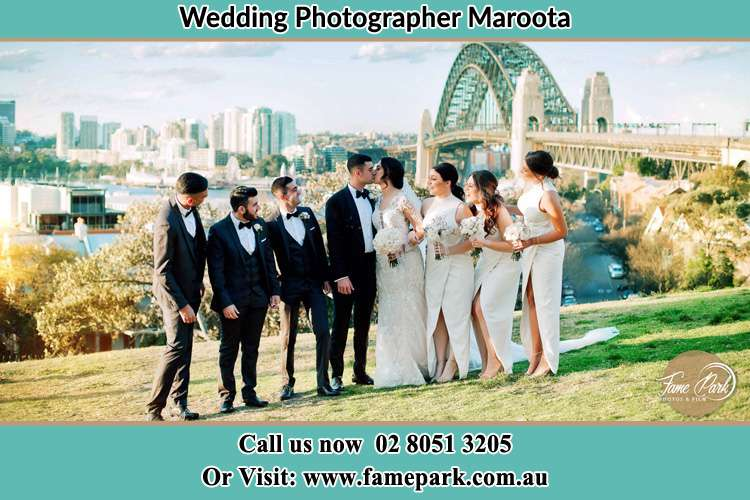 Photo of the Groom and the Bride kissing with the entourage under the bridge Maroota NSW 2756