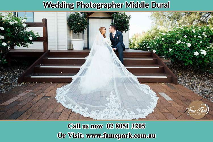 Photo of the Bride and the Groom looking each other while sitting at the staircase Middle Dural NSW 2158