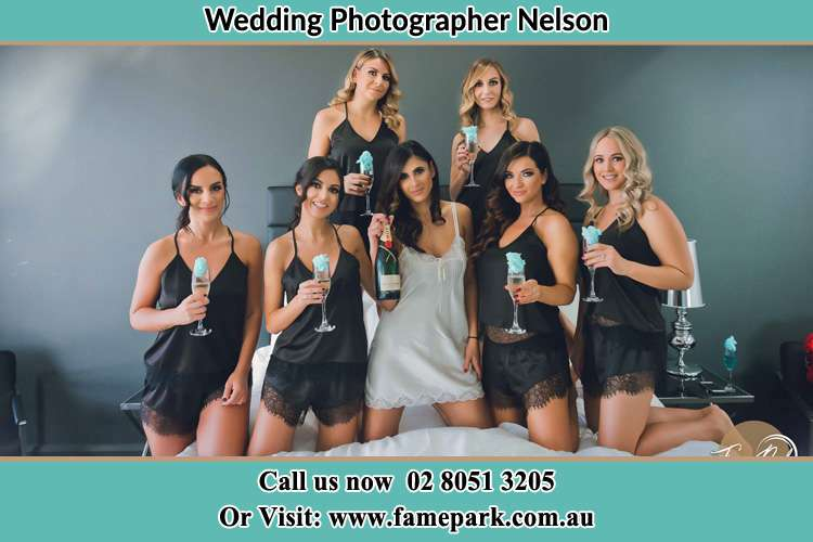 Photo of the Bride and the bridesmaids wearing lingerie and holding glass of wine on bed Nelson NSW 2765
