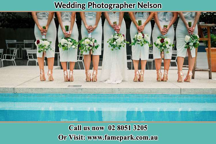 Behind photo of the Bride and the bridesmaids holding flower near the pool Nelson NSW 2765