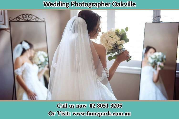 Photo of the Bride holding flower in front of the mirrors Oakville NSW 2765
