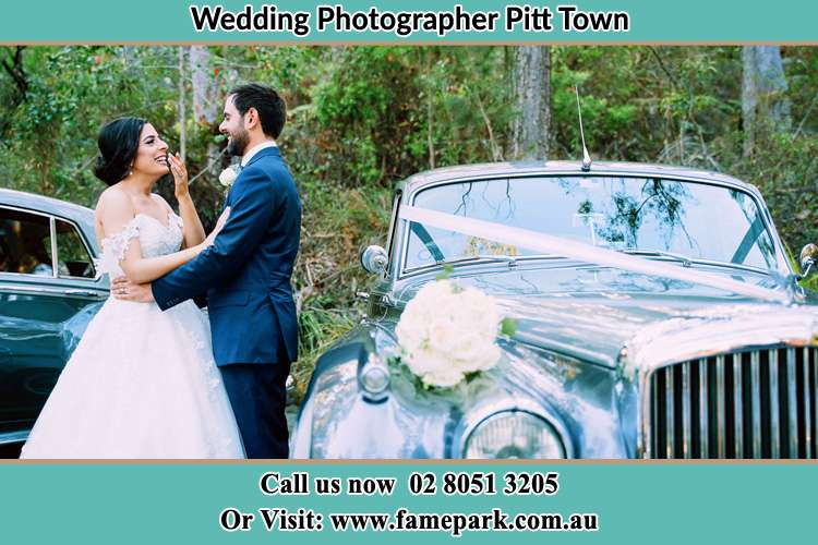 Photo of the Bride and the Groom looking each other besides the bridal car Pitt Town NSW 2756