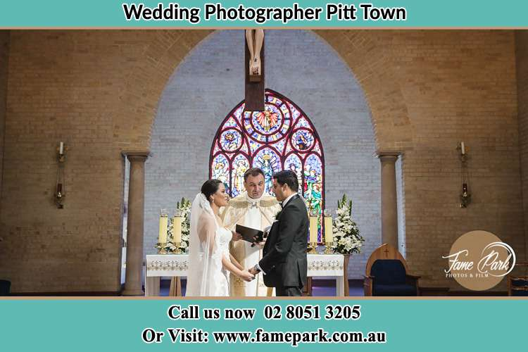 Photo of the Bride and the Groom with the Priest at the altar Pitt Town NSW 2756