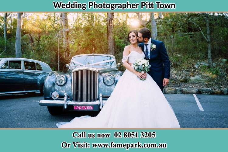 Photo of the Bride kiss by the Groom at the front of the bridal car Pitt Town NSW 2756