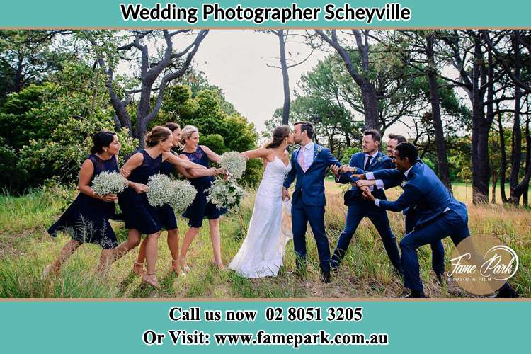 Photo of the Bride and the Groom kissing while teasing by the entourage Scheyville NSW 2756