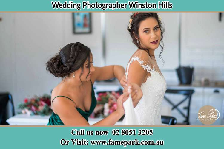 Photo of the Bride assisting by the bridesmaid to fit her wedding gown Winston Hills NSW 2153